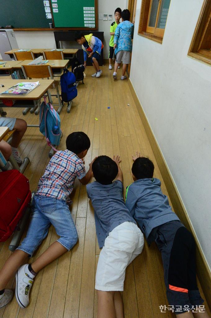11일 충남의 한 초등학교 1학년 놀이시간. 아이들이 교실 한켠 비좁은 공간에 엎드려 미니카 놀이를 하고 있다.