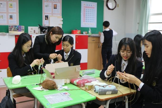 강은이 교사가 학생들에게 뜨게질 하는 법을 가르쳐주고 있다.